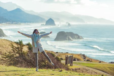 Cheerful female standing on coastline Stock Photo