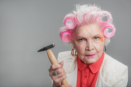 Grumpy senior female in curlers staring at camera