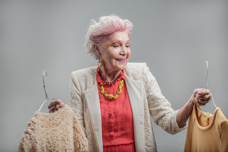 Smiling senior woman deciding what to put on Stock Photo