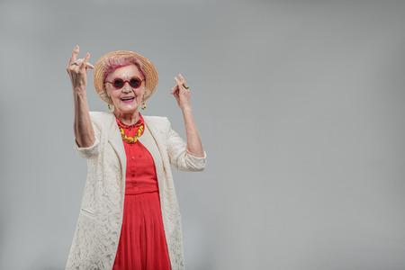 Emotional elderly woman gesturing positively