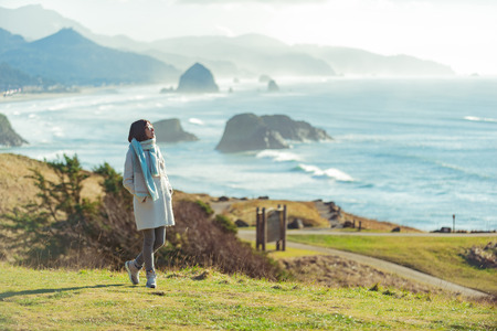 Thoughtful female standing on coastline Stock Photo