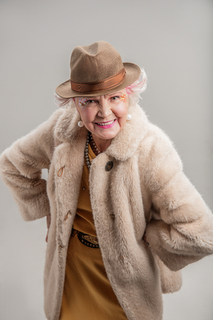 Good times. Portrait of Smiling senior woman with white hair in fur coat and hat looking at camera while posing for fun. isolated
