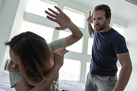 inexplicable: Inexplicable anger. Angry man hanging over scared woman with risen hand Stock Photo