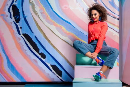 Content female wearing in bright clothes sitting on wide wooden steps Imagens
