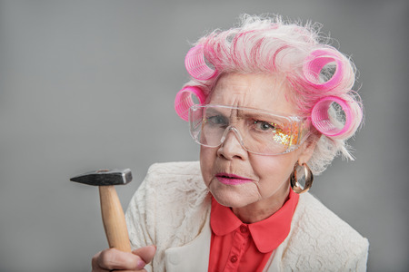 Whom are you calling old. Portrait of Stylish elderly woman in curlers holding hammer while posing at camera. isolated background Stock Photo