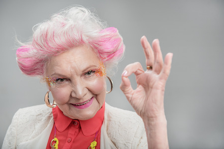すべて大丈夫です。灰色の背景に分離されたスタジオの中に立って大丈夫を示すピンクの髪と笑顔の魅力的な年配の女性 写真素材