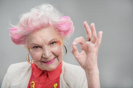 Alles is in orde. Glimlachende aantrekkelijke bejaarde die met roze haar ok tonen terwijl status in studio op grijze achtergrond wordt geïsoleerd