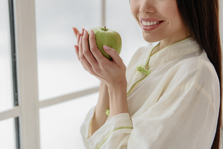 Cheerful asian woman tasting apple