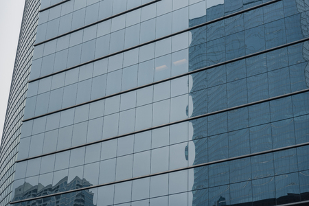 Tall buildings mirroring in other construction