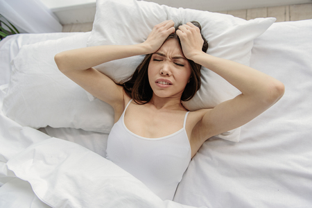 Frustrating asian woman lying in bed