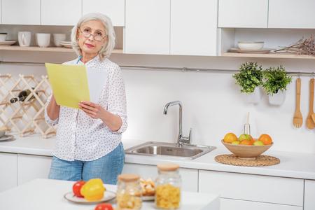 Sad senior housewife analyzing utility bills Stock Photo