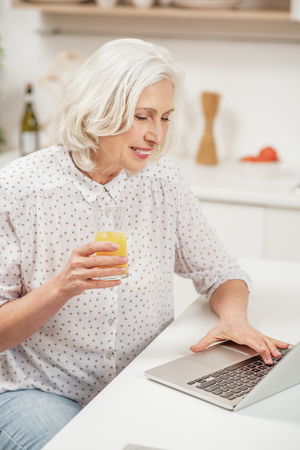Smiling old housewife using computer in kitchen