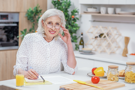 Cheerful senior housewife calculating domestic expenses Stock Photo