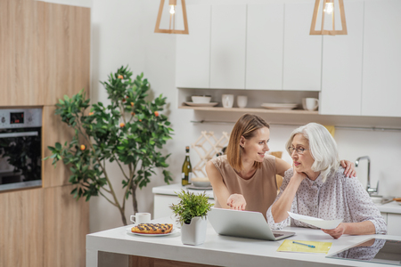 Carefree woman showing mom how computer works