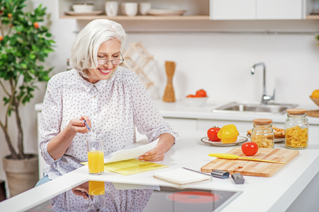 Cheerful mature housewife settling household chores Stock Photo
