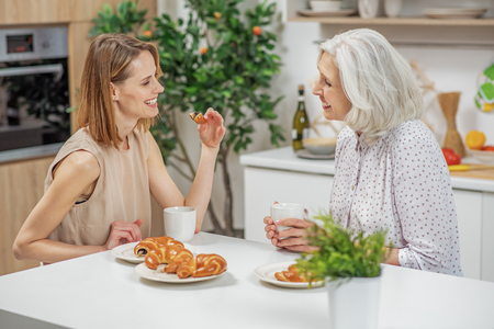 Cheerful woman having breakfast with parent Stock Photo