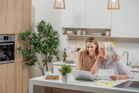 コンピューターを使用して彼女のお母さんを教える非常に若い女性