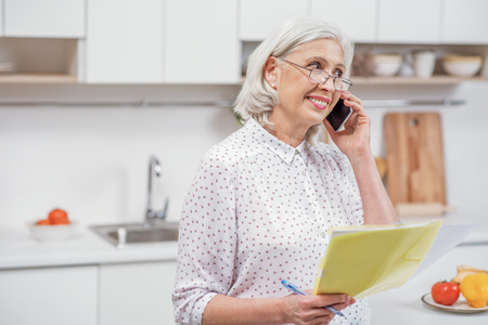 Mature woman calling utility service at home Imagens