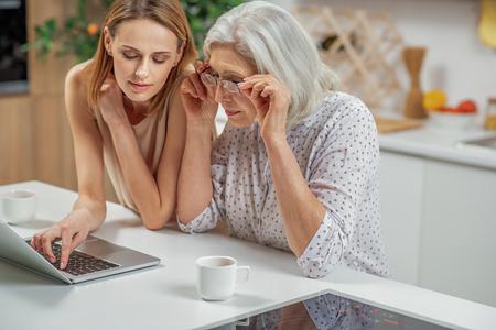 노트북을 사용하는 그녀의 어머니를 가르치는 쾌활한 아가씨