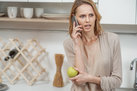 Nervous lady talking on phone in cook room