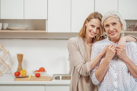 Cheerful woman embracing her senior parent in kitchen Stock Photo