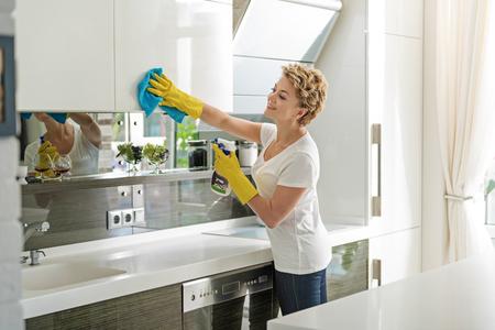 Femme joyeuse active, cuisine de nettoyage Banque d'images - 75633189