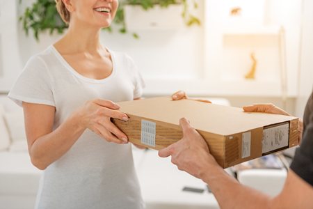 Happy laughing woman receiving parcel