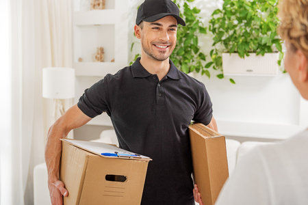 Happy smiling male person keeping boxes