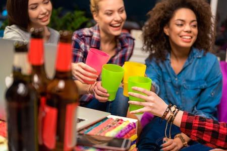 Cheerful ladies drinking beverage in room Stock Photo