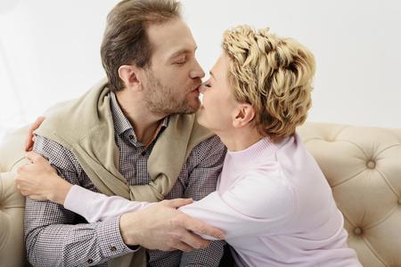 Joyful man and woman enjoying kiss