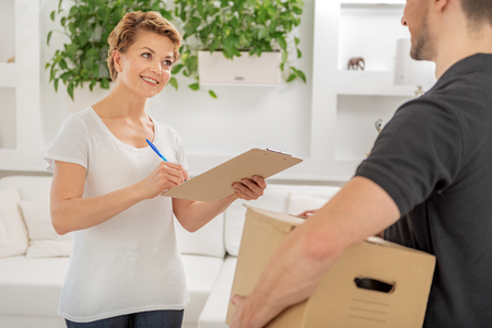 Deliveryman and woman standing in room