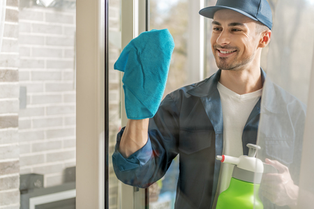 microfiber: Cheerful male person cleaning window Stock Photo
