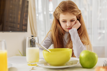 Sad female kid refuses healthy food