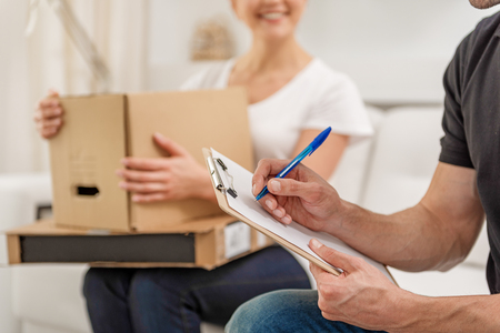 Deliveryman sitting on sofa near woman Stock Photo