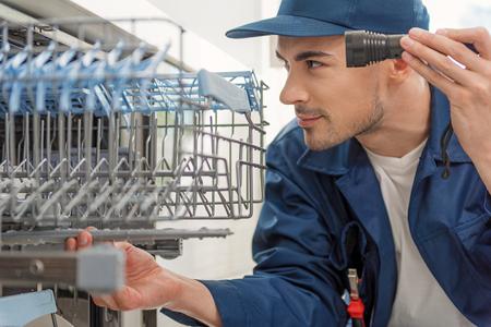 Interested man looking at kitchen appliance Reklamní fotografie