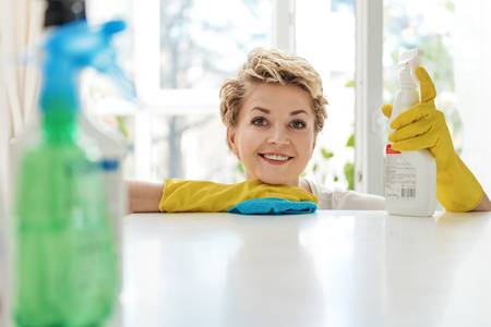 on duty: Happy smiling woman cleaning kitchen