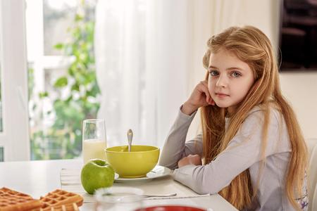 Nettes Kind, das Frühstück zu Hause essen Standard-Bild