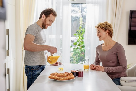 a jar stand: Happy married couple having breakfast in kitchen