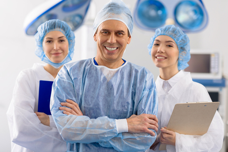 Merry surgical team in operating room Stock Photo
