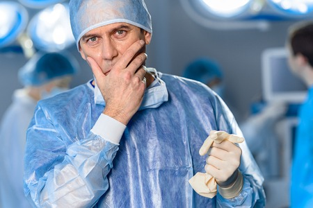 Upset male doctor in operating room Фото со стока