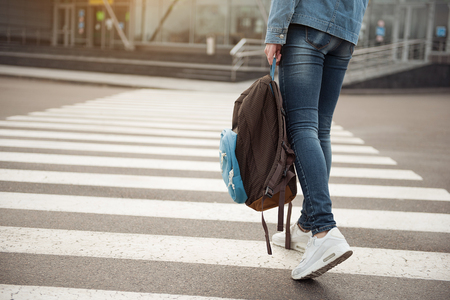 Young tourist stepping across route
