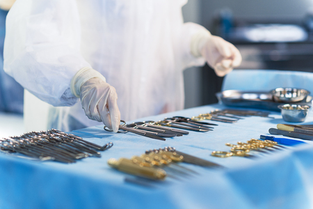 operating table: Doctor taking sterile tool for operation Stock Photo