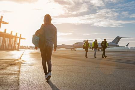 Woman walking at plane parking lot Stock Photo