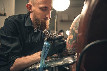 thoughtfulness: Serene male doing tattoo in salon