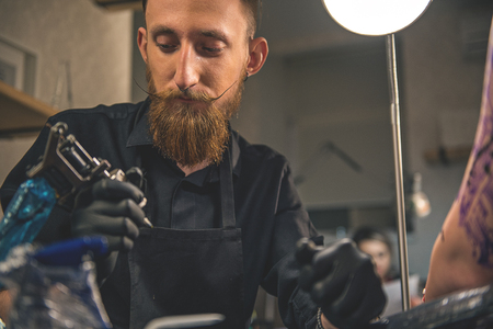 Pensive man looking at instrument in salon Stock Photo