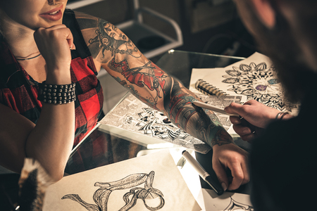 Female hand with tattoo situating on desk Stock Photo