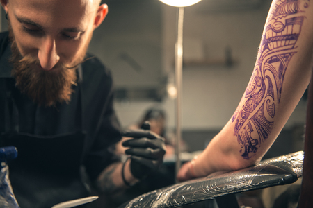 assimilate: Serene male doing tattoo on arm