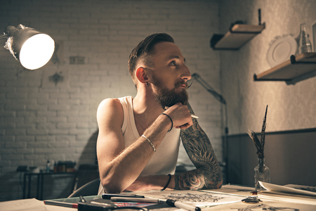thoughtfulness: Pensive bearded male painting pictures Stock Photo