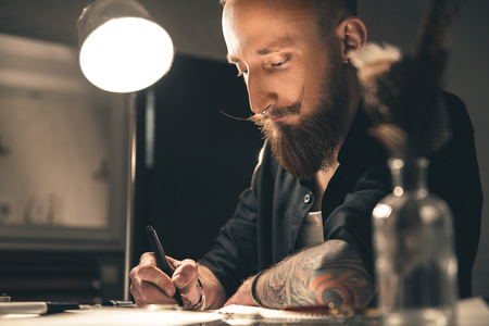 Considerate man making images at desk