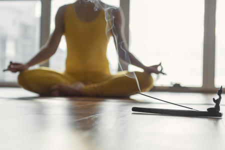 Young relaxed woman is enjoying meditation at home. She is sitting on floor in lotus position and joining fingers. Focus on incense stick burning with smoke Banco de Imagens